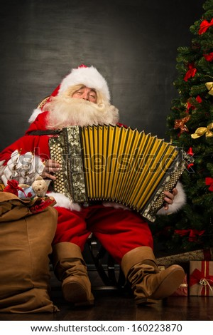 Santa Claus sitting in armchair near Christmas Tree at home and playing music on accordion