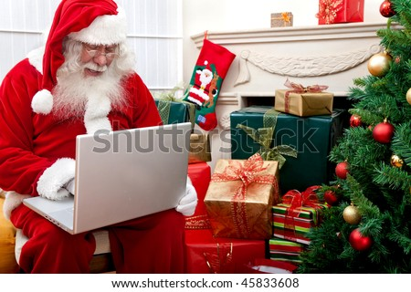 Santa Claus sitting next to a Christmas tree with a laptop