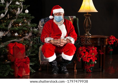 Santa Claus Sitting on a Chair and Wearing a Surgical Mask Looking at the Camera