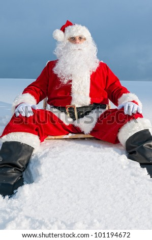 Santa Claus sitting on sunbed covered with snow