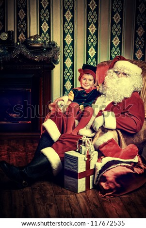 Santa Claus sitting with a little cute boy elf near the fireplace at home.