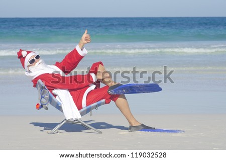 Santa Claus sitting with flippers and snorkel at beach, having fun and joy off duty at tropical holiday vacation, isolated with ocean and blue sky as background and copy space.