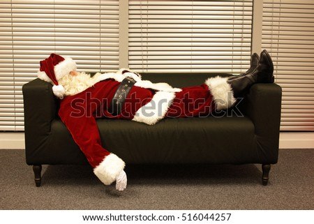 santa claus sleeping on sofa in office