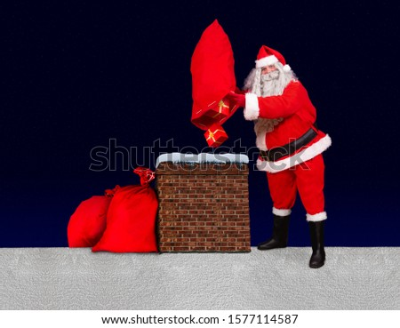 Santa Claus standing at a snowy roof and throw gifts from bag into the chimney, background of dark blue with stars. Santa upturn sack with christmas boxes to chimney.