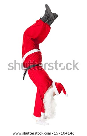 Santa Claus standing head over feet isolated on white background #157104146