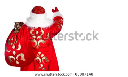 Santa Claus standing up on white background with his bag full of gifts. Photo from behind