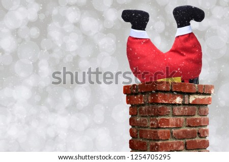 Santa Claus stuck upside down in a chimney over a silver bokeh background with snow effect.