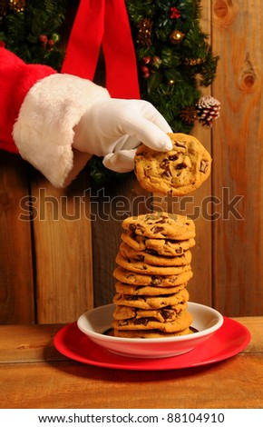 Santa Claus taking a chocolate chip cookie from large stack on plate.