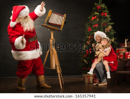 Santa Claus taking picture of family - cheerful woman with her daughter by old wooden camera at home near Christmas tree