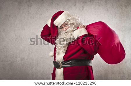 Santa Claus touching his hat and holding his sack full of presents