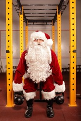Santa Claus training before Christmas in gym - kettlebells