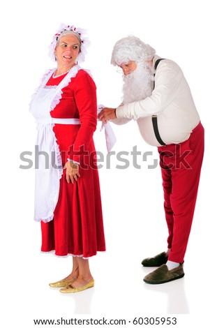 Santa Claus tying Mrs. Santa's apron while she looks on.  Isolated on white.