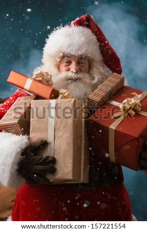 Santa Claus walking on the snow with his sack of lots of presents Winter night with snowfall