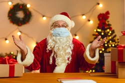 Santa Claus wearing modern medical accessory looking at camera and talking to subscribers during live stream. Father Christmas in face mask sitting at table in workshop having online video call