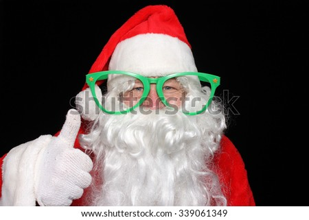 Santa Claus wears Giant Green Glasses while he poses for photos in a Photo Booth. Santa Claus humor. Santa Claus Joking around. Christmas Humor. Funny photo. Funny image. Laughing Santa.