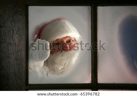 Santa Claus wipes the snow and fog away from his workshop window in the north pole to see outside and make sure his raindeer are getting ready to go to work on December 24th, Christmas Eve