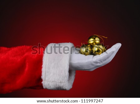 Santa Claus with a handful of gold sleigh bells over a red light to dark background. Horizontal format showing only hand and arm.
