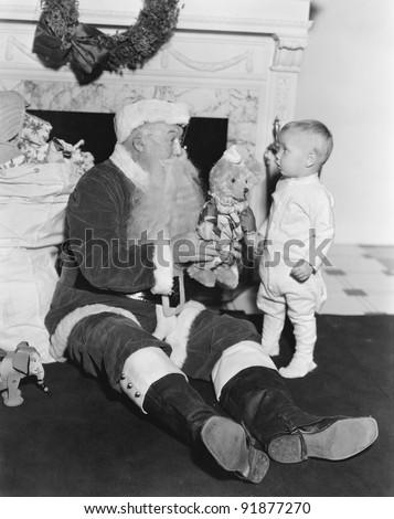 Santa Claus with a little boy and a teddy bear in front of a fire place