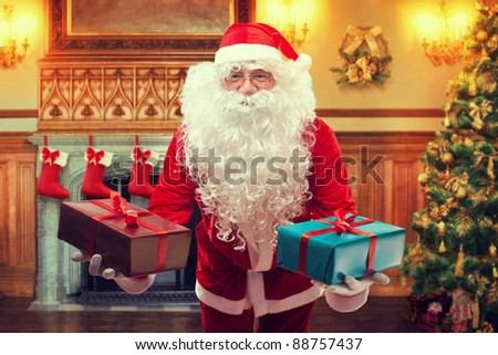 Santa Claus with gifts in decorated living room