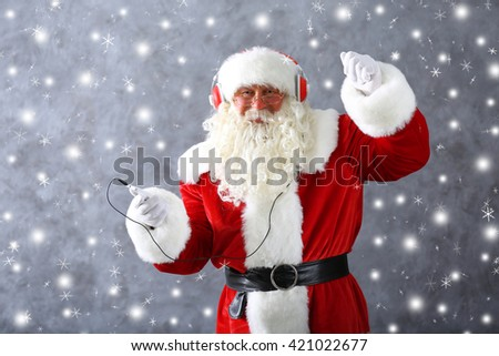 Santa Claus with headphones listening to music on gray wall background with snow effect #421022677