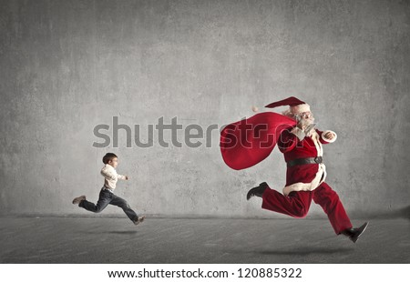 Stock Photo Santa Claus with his bag full of gifts runs away from a child who chases