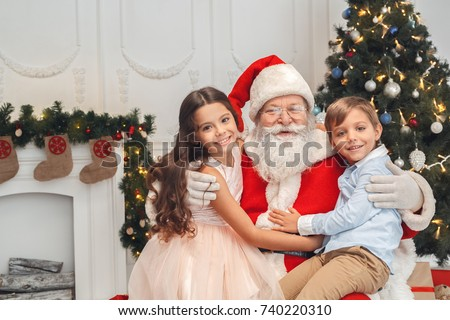 Santa Claus with kids indoors christmas celebration concept #740220310