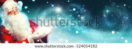 Santa Claus with magic gift in his hands. Portrait of happy Santa Claus making magic at night, Blowing Magic Christmas Stars