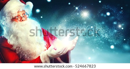 Santa Claus with magic gift in his hands. Portrait of happy Santa Claus making magic at night, Blowing Magic Christmas Stars #524667823