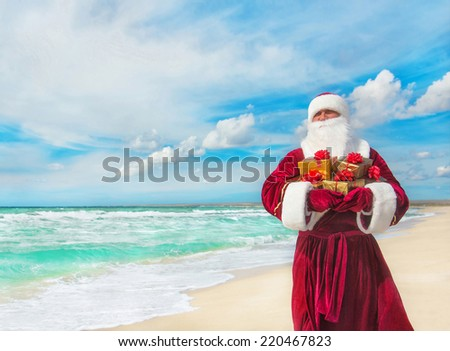 Santa Claus with many golden gifts on sea beach - christmas or happy new year concept