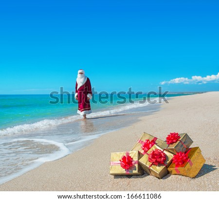 Santa Claus with many golden gifts relaxing on sandy sea beach - christmas or happy new year concept