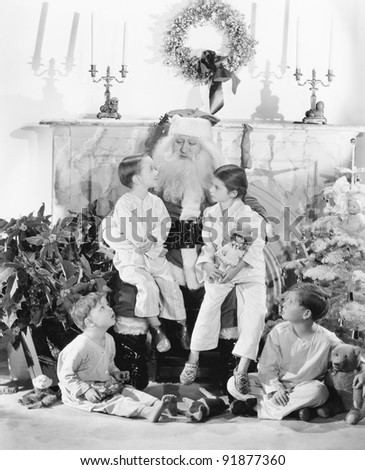 Santa Claus with presents and a group of children in front of a fire place - stock photo