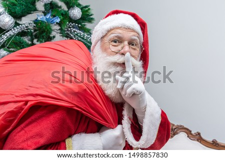 Santa Claus with red sack keeping forefinger by his mouth and looking at camera. Shh! Keep secret. Silent confidential, privacy quiet, shush hissing hush concept. Funny Saint Nicholas.
