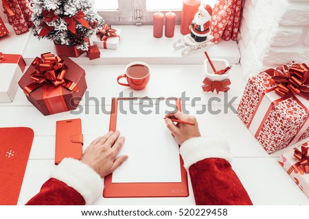Santa Claus working at desk and writing on a blank sheet on a clipboard, he is getting ready for Christmas, point of view shot