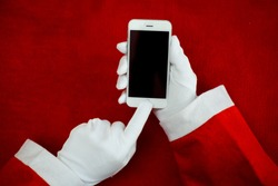 Santa Claus working using smartphone screen on red table fabric texture background surface. Close up top view on hands. Happy New Year and Merry Christmas design