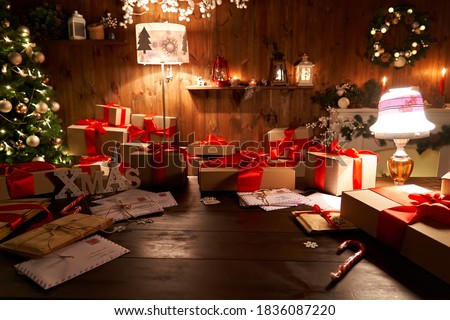Santa Claus workshop home wooden decorated table with Merry Christmas tree, decor, wrapped gifts presents boxes on holiday eve in cozy home interior late in night with lamp light on xmas background.