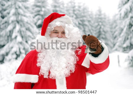 santa clause in a snowy forest is ringing the christmas bell