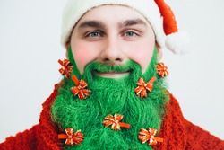Santa Clause in red clothes with green beard horizontal. Happy New Year. Marry Christmas. Decorated beard. Green beard decorated with red bows.  Christmas tree