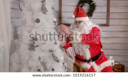 Stock Photo santa decorates the Christmas tree with toys 4k