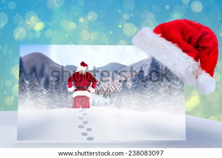 Santa delivery presents to village against blue abstract light spot design