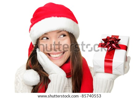 Santa girl holding christmas gift. Young happy woman in santa hat looking sideways showing Christmas present isolated on white background. Beautiful cute young santa woman.