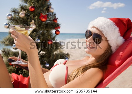 Santa girl in Christmas vacation on the beach with a glass of martini