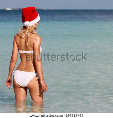Santa Girl on Tropical Beach. Beautiful blonde young woman in red Christmas Hat and bikini from behind enjoying blue sea. Christmas Vacation. Concept