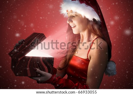 Santa girl, opens the gift with magical light going from it