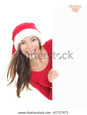 Santa girl peeking from behind blank sign billboard. Advertising photo of young smiling Christmas woman in Santa hat showing paper sign. Asian / Caucasian female model isolated on white background