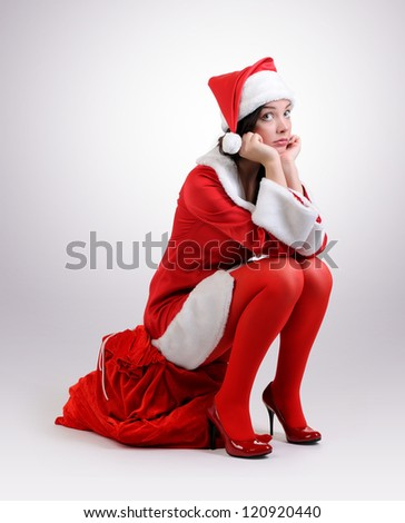Santa girl with a red bag of gifts