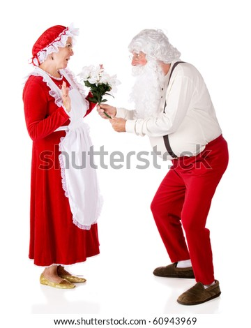 Santa giving a bouquet of white poinsettias to Mrs. Claus.  Isolated on white.