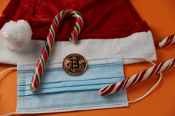 Santa hat and Bitcoin coin, colored candies on an orange background