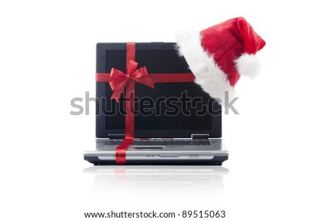 Santa hat and ribbon with laptop computer isolated on white - stock photo