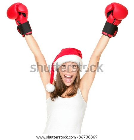 Santa hat christmas woman celebrating wearing boxing gloves. Fitness or boxing shopping day concept. Winner energy from asian caucasian female model isolated on white background.
