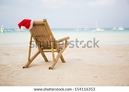 Santa hat on chaise longue on white sand beach